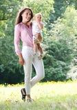 抱着婴孩的美丽的妇女在公园 免版税库存图片