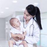 抱着婴孩的年轻女性儿科医生 库存图片