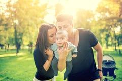 抱着婴孩, 3个月新出生和亲吻他的妈妈和爸爸 与父亲、母亲和婴儿的愉快的家庭 葡萄酒作用 免版税库存图片