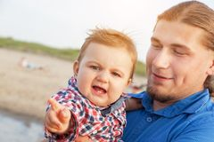 抱他的海滩的年轻父亲孩子 滑稽的表达式 库存图片