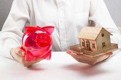 抵押或储款概念 拿着钱箱和微型房子的手 免版税库存照片