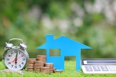 抵押计算器、蓝色房子模型和堆与闹钟的硬币金钱在自然绿色背景,利息和 免版税图库摄影