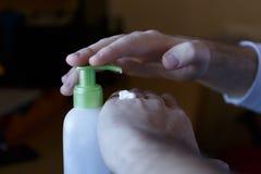 抹上在一个奶油色瓶子的损坏的手上的润肤霜与分配器 库存图片
