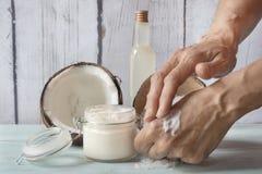 抹上自创椰子和玫瑰奶油的人的手 库存图片