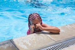 抹从眼睛的青春期前的女孩水,当游泳在水池时 库存照片