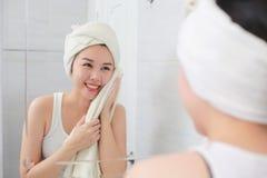 抹她的面孔的年轻亚裔妇女与毛巾在卫生间里 免版税库存照片
