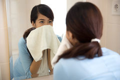 抹她的面孔的美丽的亚裔妇女与毛巾,看mir 免版税库存图片
