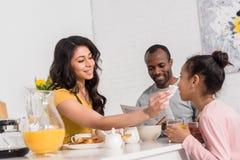 抹小女儿的面孔愉快的母亲在早餐以后,当父亲读书报纸时 免版税库存照片