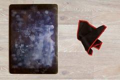 抹指纹和油膏的布料在片剂屏幕上 库存照片