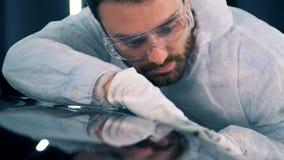 抹汽车的光滑的表面的过程由一位男性技工举行了 股票录像