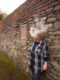 抽一根电子香烟的成熟妇女 免版税库存图片