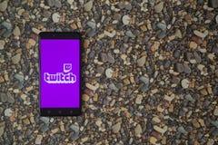 抽动在智能手机的商标在小石头背景  图库摄影