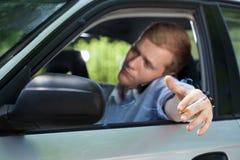 抽在汽车的商人一根香烟 免版税库存图片
