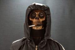 抽在黑背景,香烟的人的头骨一根香烟非常危险为人 穿上请抽t 万圣夜天 免版税库存图片
