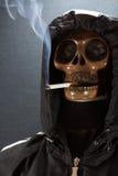 抽在黑背景,香烟的人的头骨一根香烟非常危险为人 穿上请抽t 万圣夜天 免版税库存照片