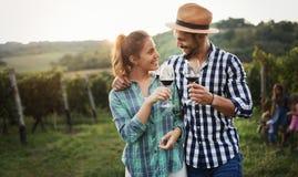 抽样和品尝酒的人们在葡萄园里 库存图片