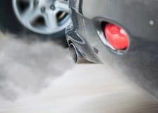 抽汽车管子尾气,从汽车的烟导致污染 库存图片