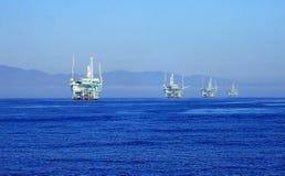 抽油装置线在离从海洋射击的加利福尼亚海岸的附近 库存照片