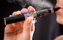 抽烟与电子香烟的妇女 免版税库存图片