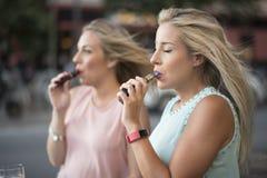 抽烟从蒸发器管子的两个白肤金发的姐妹 免版税图库摄影