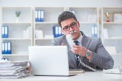 抽烟在办公室的商人在工作 免版税图库摄影