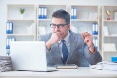 抽烟在办公室的商人在工作 库存照片
