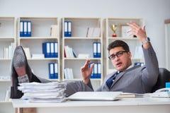抽烟在办公室的商人在工作 库存图片