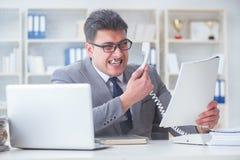 抽烟在办公室的商人在工作 免版税库存照片
