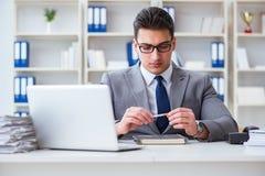 抽烟在办公室的商人在工作 免版税库存图片