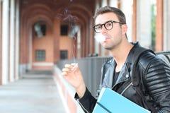 抽烟在校园关闭的学生  免版税库存图片
