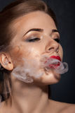 抽烟在演播室的秀丽成年女性 免版税库存图片