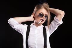 抽烟在黑背景的热的白肤金发的性感的妇女 免版税库存图片