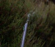 抽烟的桶在射击以后的猎枪 免版税库存照片