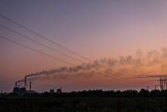 以抽烟的烟囱为背景的日落 库存照片