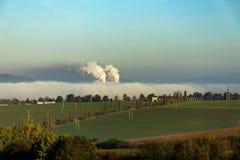 抽烟的烟囱从在薄雾掩藏的工厂 库存图片