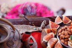 抽烟的香火 印地安早餐无花果和坚果在一张木桌上 静物画用热的通入蒸汽的绿茶 免版税库存照片