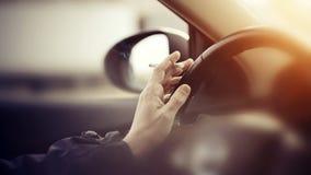 抽烟的香烟,当驾驶时 免版税库存照片