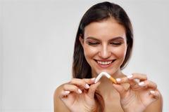 抽烟的终止 打破在一半的美丽的妇女香烟 免版税库存图片