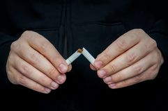 抽烟的Quit -击碎香烟的男性手 免版税库存照片