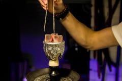 抽烟的shisha和休闲的水烟筒热的煤炭在东部样式背景中 碗用烟草和煤炭 水烟筒墙纸 免版税库存图片