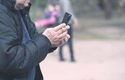 抽烟老的人和使用他的电话 免版税库存图片