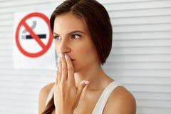 抽烟 有禁烟标志的美丽的妇女在背景 库存照片