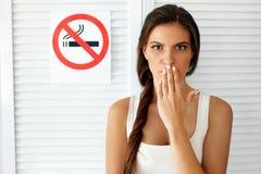 抽烟 有禁烟标志的美丽的妇女在背景 免版税库存照片