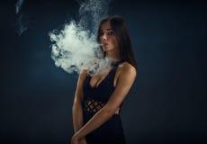 抽电子香烟的一件黑礼服的性感的女孩 免版税库存图片