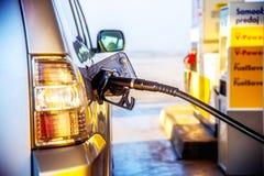 抽的汽油在汽车刺激在加油站 蓝色闭合的离开的门公务电梯绘了工作者 库存图片