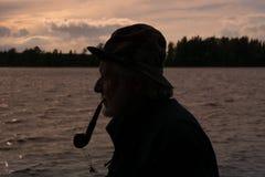 抽管子的一位老渔夫的侧视图剪影 免版税库存图片
