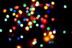 抽象与电灯泡的圣诞节轻的五颜六色的链子-被弄脏的背景 免版税图库摄影