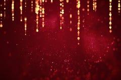 抽象与bokeh和金黄小条,情人节爱欢乐假日的事件的圣诞节梯度红色背景 免版税库存照片