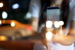 抽象人民通过玻璃拍照片由巧妙的电话在街道夜 免版税库存图片