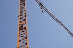 抽象图象,一部分的胳膊机械建筑用起重机有蓝天背景 免版税库存图片